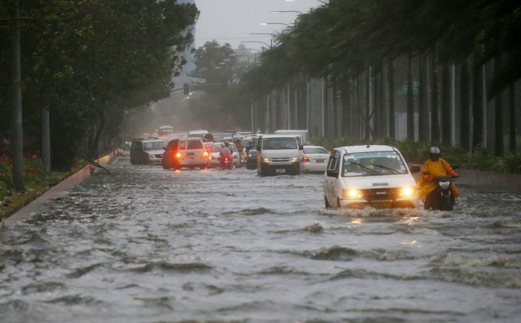 Motorists negotiate a flooded street following heavy rains and strong winds brought about by Typhoon Mangkhut which barreled into northeastern Philipp