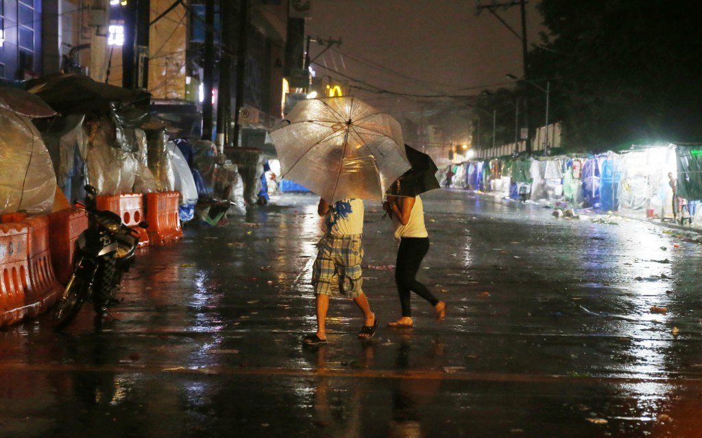 Commuters brave the rain and strong winds brought about by Typhoon Mangkhut which barrelled into northeastern Philippines before dawn Saturday, Sept.
