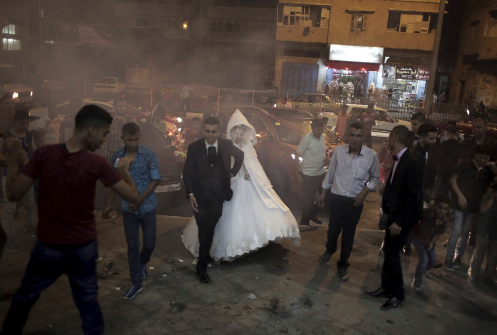 FILE - In this July 31, 2016 photo, Palestinian groom Saed Abu Aser, and his bride, Falasteen, walk into the wedding hall, in Gaza City. (AP Photo/Kha