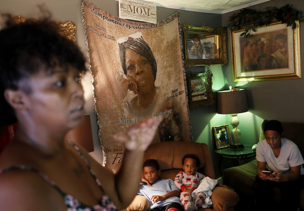 Nichole Worley, left, talks next to a blanket decorated with an image of her late mother Mary DeLane McBrayer, as her niece Tamara Small, right, and g