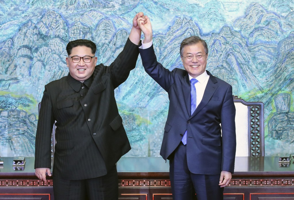 FILE - In this April 27, 2018 file photo, North Korean leader Kim Jong Un, left, and South Korean President Moon Jae-in raise their hands after signin