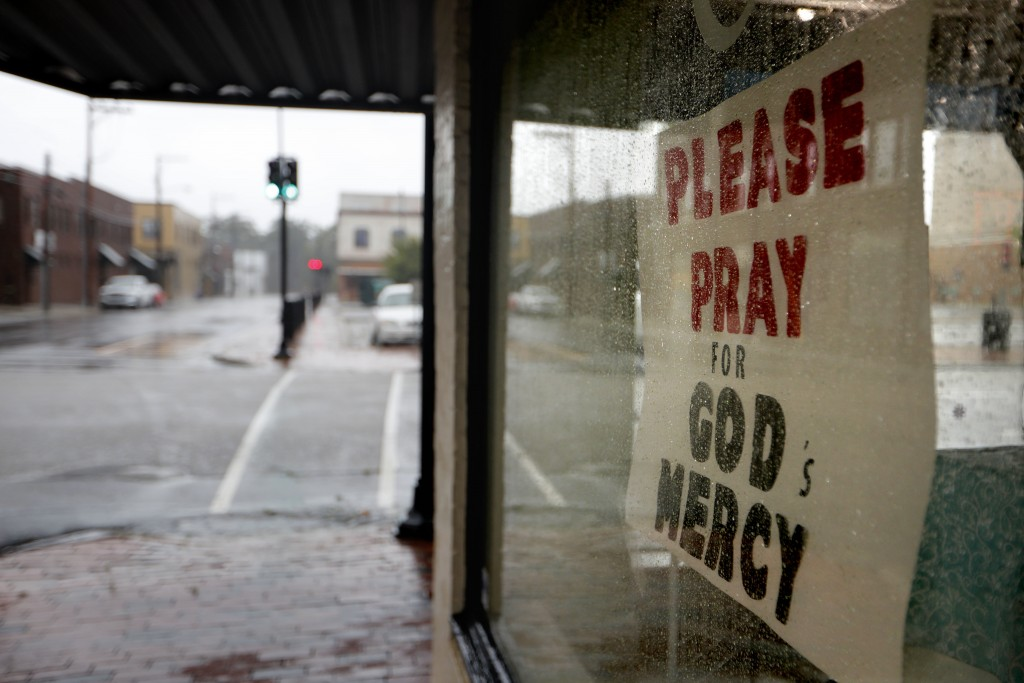A sign with a message regarding Hurricane Florence hangs in a storefront in Lumberton, N.C., Friday, Sept. 14, 2018. The rural town, battered by the c