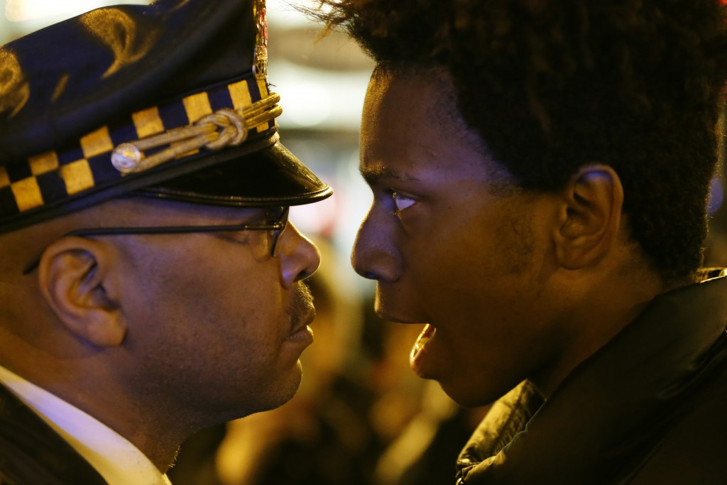 "FILE - In this Wednesday, Nov. 25, 2015 file photo, Lamon Reccord, right, stares and yells, ""Shoot me 16 times,"" at a Chicago police officer as he and"