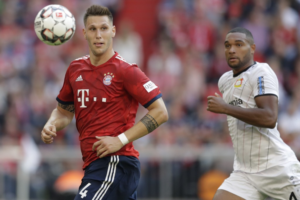 Bayern's Niklas Suele, left, and Leverkusen's Jonathan Tah, right, challenge for the ball during the German Bundesliga soccer match between FC Bayern