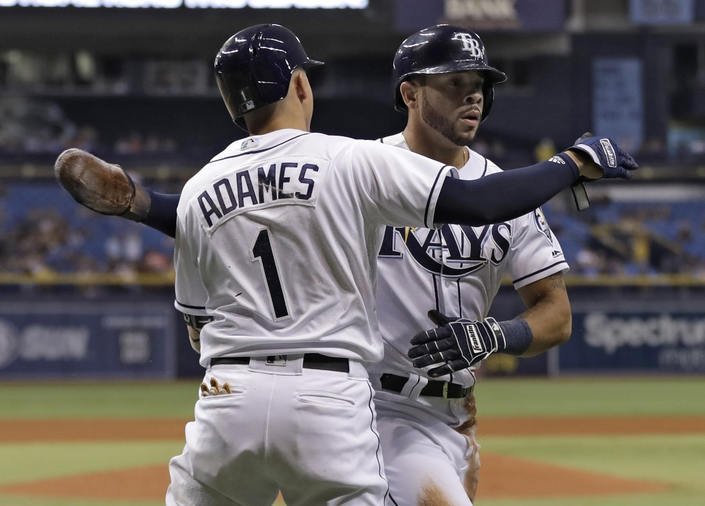 Tampa Bay Rays' Tommy Pham, right, hugs on-deck batter Willy Adames after scoring on an RBI single by Joey Wendle off Oakland Athletics pitcher Edwin