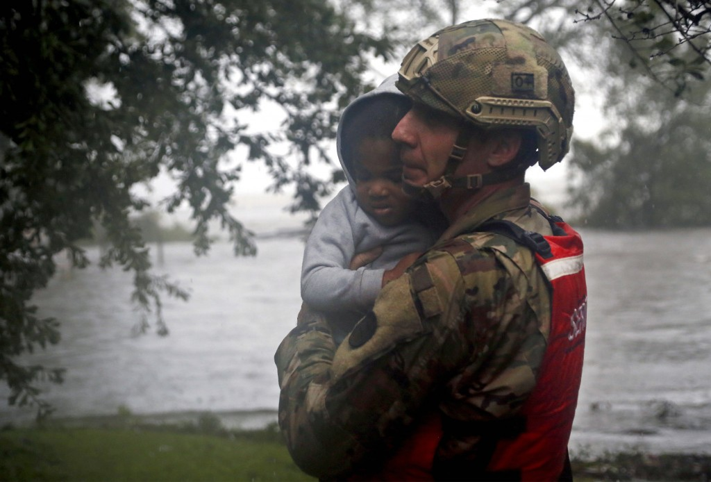Rescue team member Sgt. Nick Muhar, from the North Carolina National Guard 1/120th battalion, evacuates a young child as the rising floodwaters from H