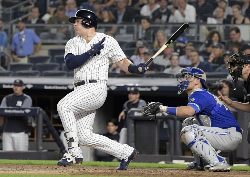 New York Yankees' Luke Voit hits a two-RBI double as Toronto Blue Jays catcher Luke Maile, right, looks on during the first inning of a baseball game