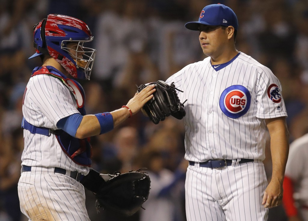 Chicago Cubs' Jorge De La Rosa, right, and Victor Caratini celebrate their win over the Cincinnati Reds at the end of a baseball game Friday, Sept. 14