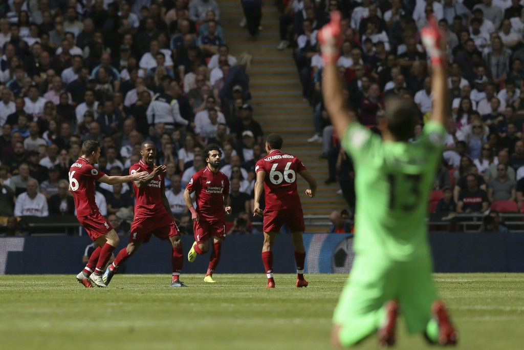 Liverpool's Georginio Wijnaldum, 2nd from left, reacts as he celebrates with team members after scoring his side opening goal during the English Premi