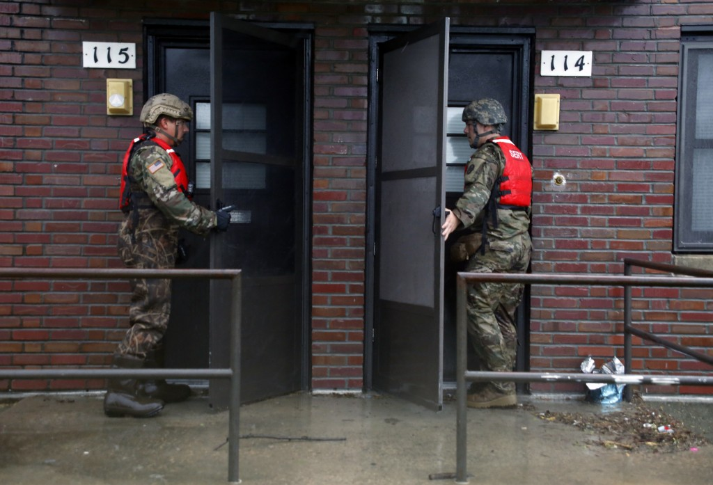 Rescue team members from the North Carolina National Guard 1/120th battalion go door-to-door as they evacuate residents in an apartment complex threat