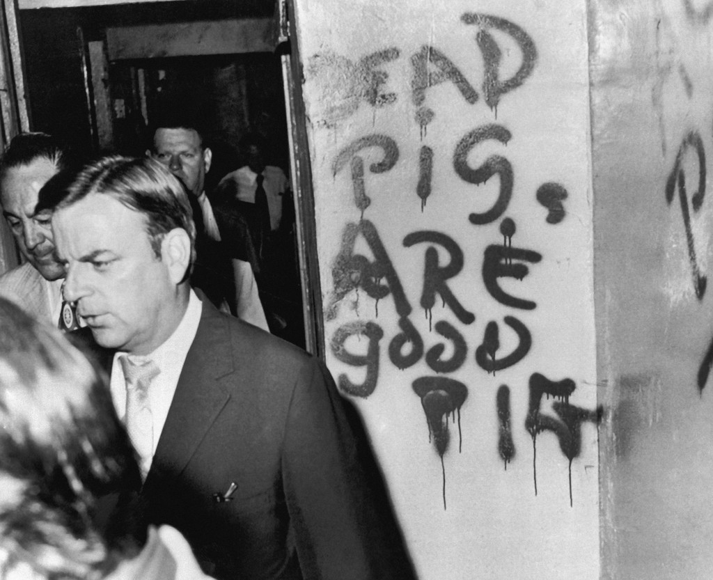 FILE - In this July 11, 1972 file photo, State's Attorney Edward V. Hanrahan walks past graffiti on wall of a West Side apartment in Chicago, in which