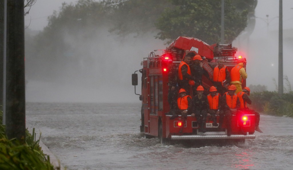 Fire rescuers head to low-lying areas in Manila under heavy rains and strong winds brought about by Typhoon Mangkhut which also barreled into northeas