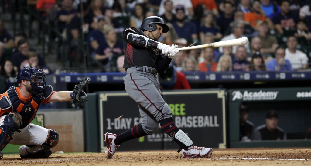 Arizona Diamondbacks' Jon Jay, right, hits a triple to score Nick Ahmed as Houston Astros catcher Brian McCann reaches for the pitch during the eighth