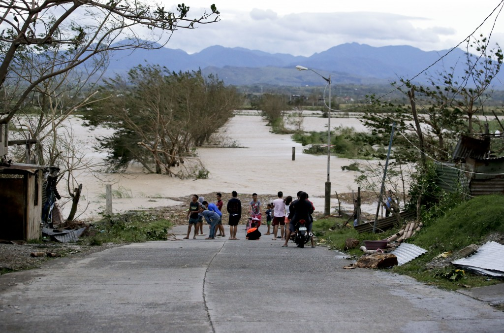 FILE - In this Saturday, Sept. 15, 2018, photo, residents stand by a flooded road following the onslaught of Typhoon Mangkhut in Tuguegarao City in Ca...