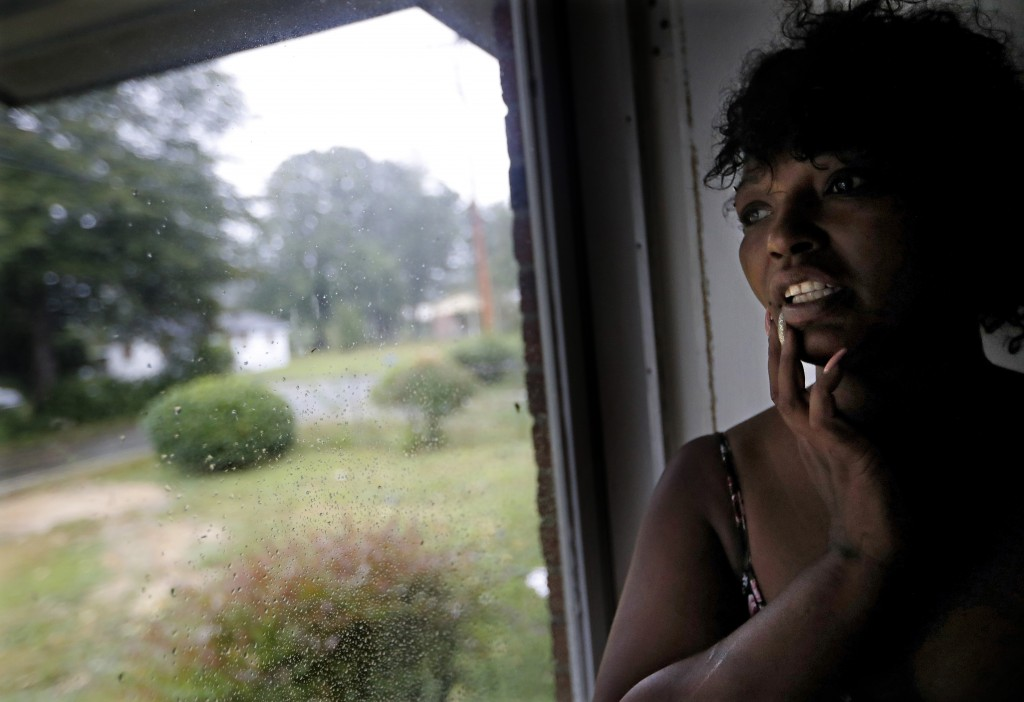 Nichole Worley looks out from her home in Lumberton, N.C., Friday, Sept. 14, 2018, as rains from Hurricane Florence threaten the neighborhood with flo
