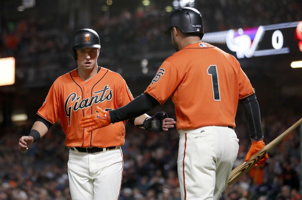 San Francisco Giants' Joe Panik, left, is congratulated by teammate Gregor Blanco (1) after scoring a run on a Austin Slater single against the Colora