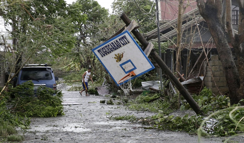 FILE - In this Saturday, Sept. 15, 2018, file photo, a resident walks beside a toppled basketball court after Typhoon Mangkhut barreled across Tuguega...