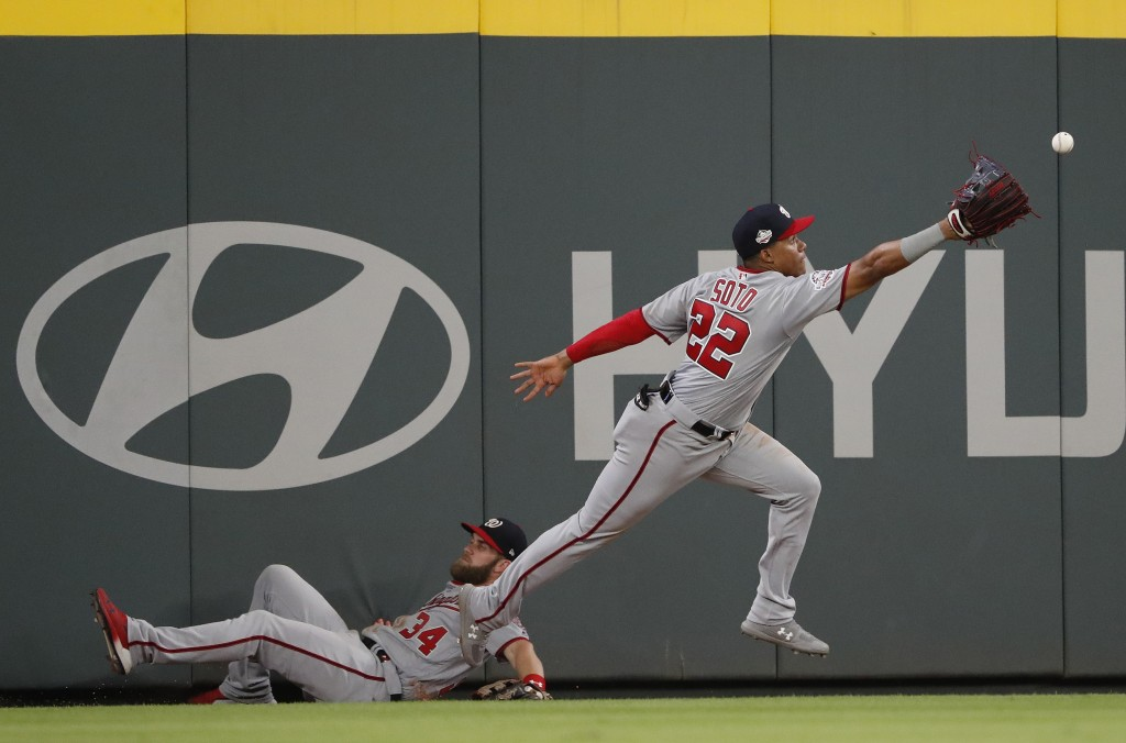 Washington Nationals left fielder Juan Soto (22) reaches for a ball hit for a triple by Atlanta Braves' Ronald Acuna Jr., as centerfielder Bryce Harpe
