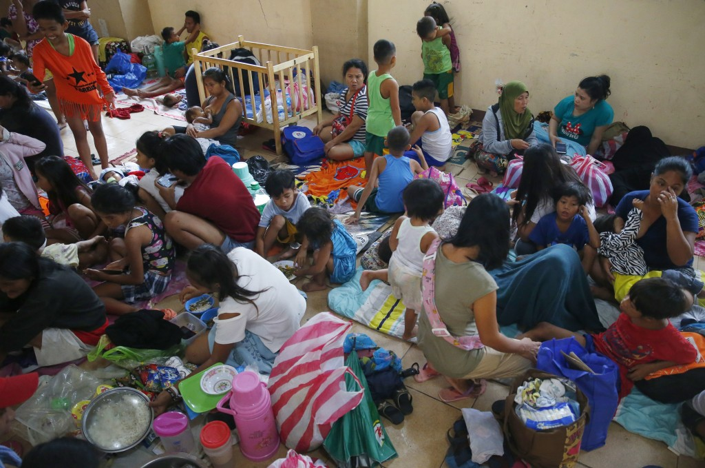 Residents living along the coastal community of Baseco seek temporary shelter at an evacuation center in the onslaught of Typhoon Mangkhut which barre