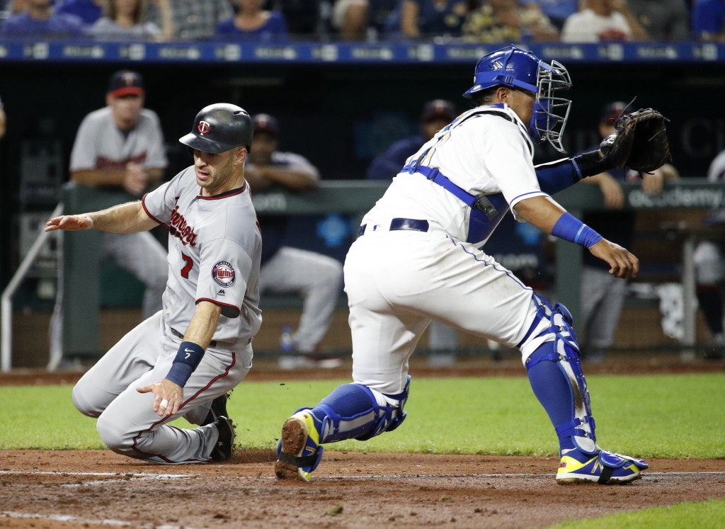 Minnesota Twins' Joe Mauer (7) beats a tag by Kansas City Royals catcher Salvador Perez to score on a single by Jake Cave during the fifth inning of a
