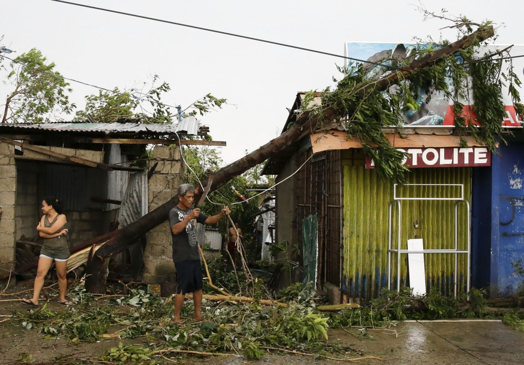 FILE - In this Saturday, Sept. 15, 2018, file photo, a resident cleans up pieces from a tree that was toppled by strong winds from Typhoon Mangkhut as