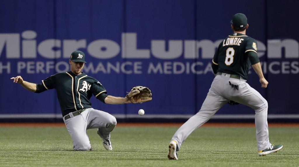 Oakland Athletics right fielder Stephen Piscotty and second baseman Jed Lowrie (8) can't get to a single by Tampa Bay Rays' Mallex Smith during the fi