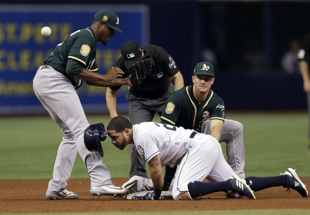Tampa Bay Rays' Tommy Pham, center, slides into second base with a double as the ball gets away from Oakland Athletics pitcher Edwin Jackson, left, an