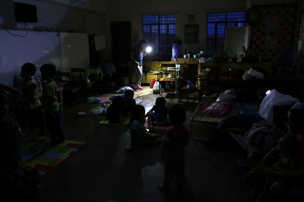 A woman uses a flashlight inside a temporary evacuation center as electricity was shut-off following the onslaught of Typhoon Mangkhut in Tuguegarao c