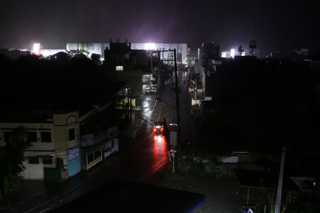 A lone vehicle navigates the road as strong winds and rain from Typhoon Mangkhut batter Tuguegarao city, Cagayan province, northeastern Philippines la