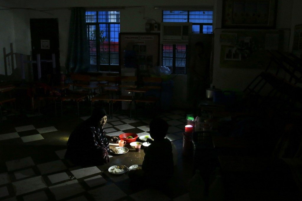 A woman and her son eats a meal using a flashlight inside a temporary evacuation center as electricity was shut-off following the onslaught of Typhoon