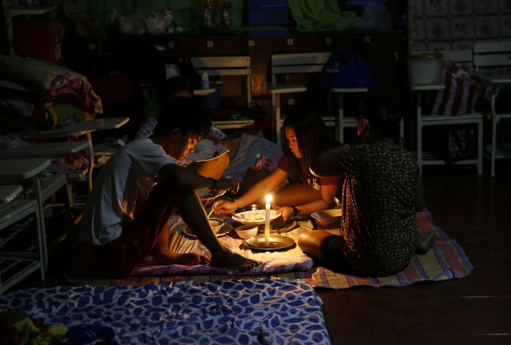 FILE- In this Saturday, Sept. 15, 2018, photo, a family shares a meal using a flashlight inside a temporary evacuation center as electricity was shut-