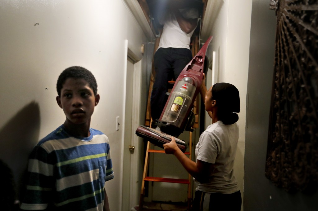 Tamara Small passes a vacuum to her uncle, Milton Johnson, as her son, Tylik Miles, helps the family pack belongings in the attic in Lumberton, N.C.,