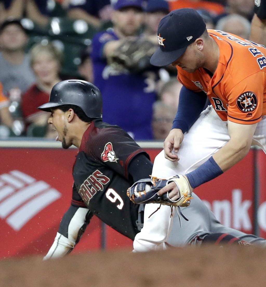 Arizona Diamondbacks' Jon Jay (9) slides safely into third after hitting an RBI triple as Houston Astros third baseman Alex Bregman reaches to tag him...
