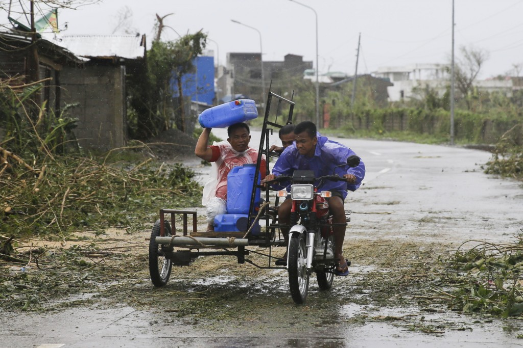 A man uses a water container to shield him from rain brought about by Typhoon Mangkhut as it barreled across Tuguegarao city, Cagayan province, northe...