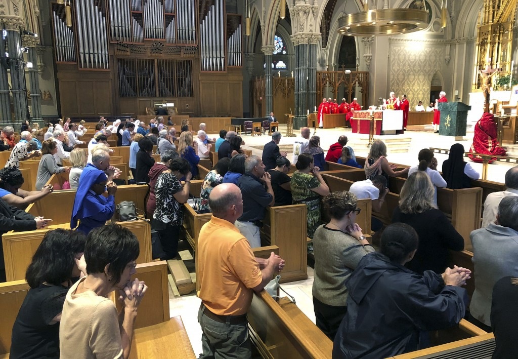 Parishioners kneel as Providence diocese Bishop Thomas Tobin, right begins Mass at the Cathedral of Saints Peter and Paul in Providence, R.I., Friday,