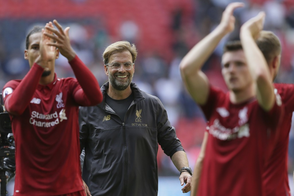 Liverpool's coach Jurgen Klopp center, celebrates with Liverpool's players after winning the English Premier League soccer match between Tottenham Hot