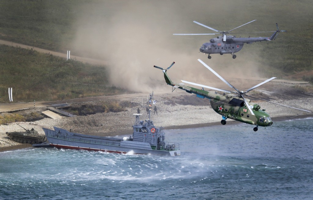 A Russian navy landing vessel unloads an armored vehicle as military helicopters fly overhead during Russian military maneuvers Vostok 2018 on the tra
