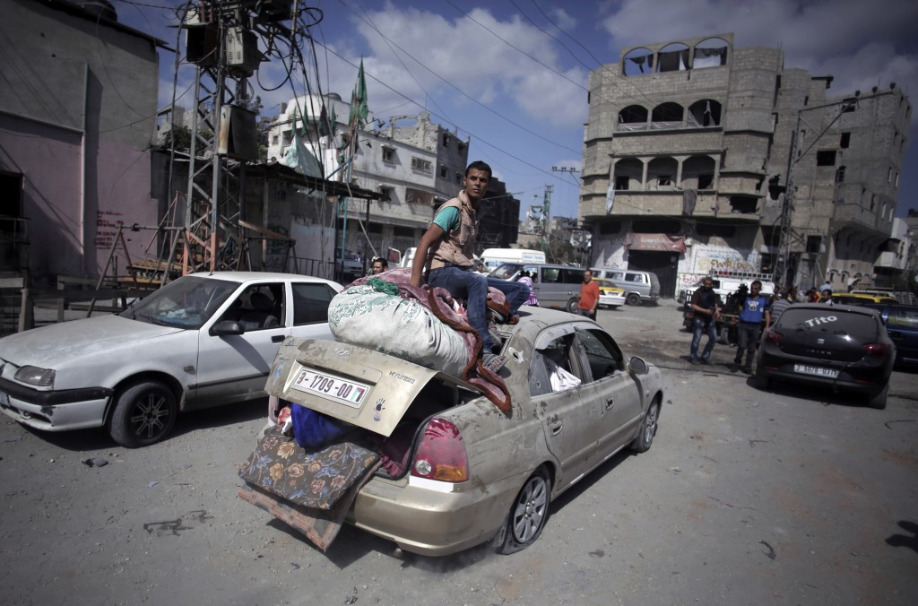 FILE - In this July 26, 2014 file photo, Palestinians salvage what little of their belongings they could from their homes during a 12-hour cease-fire