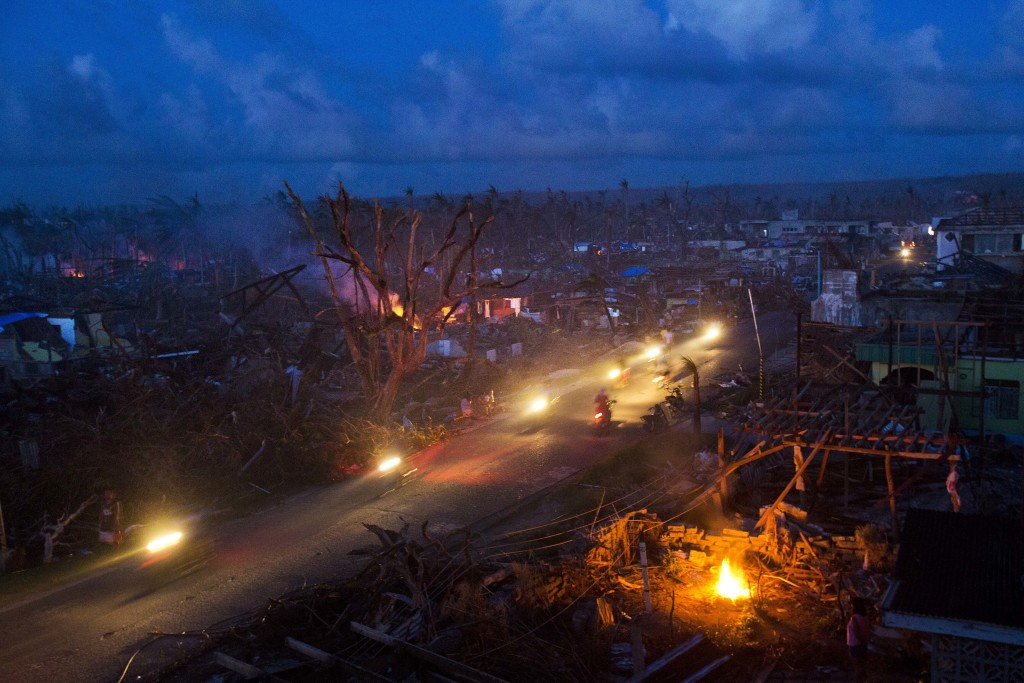 FILE - In this Nov. 14, 2013, file photo Typhoon Haiyan survivors ride motorbikes through the ruins of the destroyed town of Guiuan, Philippines. Fili...