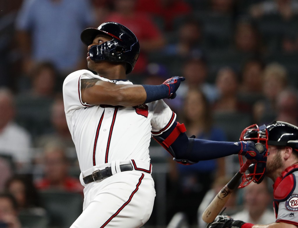 Atlanta Braves' Ronald Acuna Jr., left, follows through on a two-run base hit in the second inning of a baseball game against the Washington Nationals