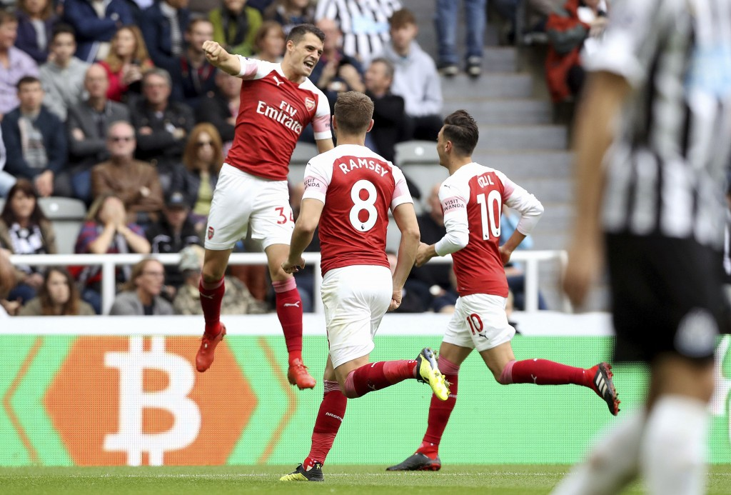 Arsenal's Granit Xhaka, left, celebrates scoring his side's first goal of the game with teammates, during the English Premier League soccer match betw