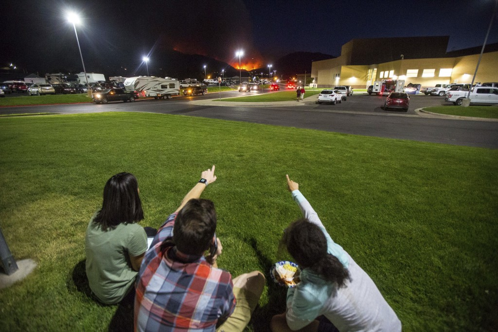 In this Thursday, Sept. 13, 2018, photo, residents watch a wildfire burning from outside Salem Hills High School in Salem, Utah. (Qiling Wang/The Dese