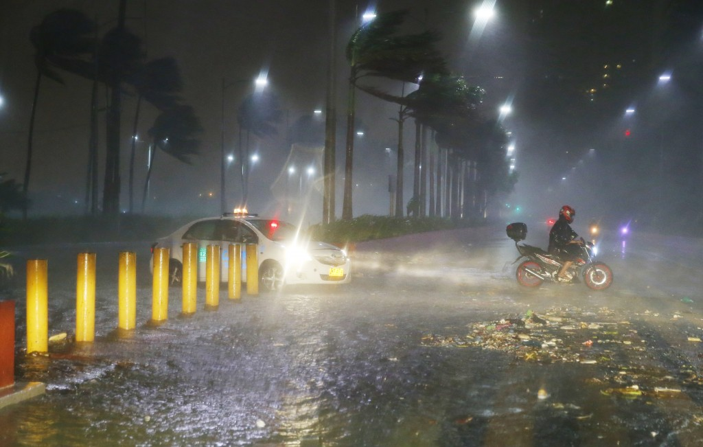 Motorists avoid a flooded street as heavy rains and strong winds brought about by Typhoon Mangkhut barrelled into northeastern Philippines before dawn