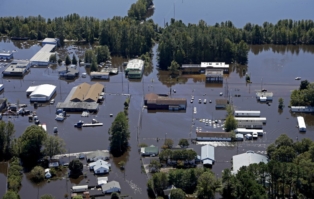 FILE - In this Oct. 12, 2016, file photo, homes and businesses are surrounded by floodwaters from Hurricane Matthew in Lumberton, N.C. The rural town,
