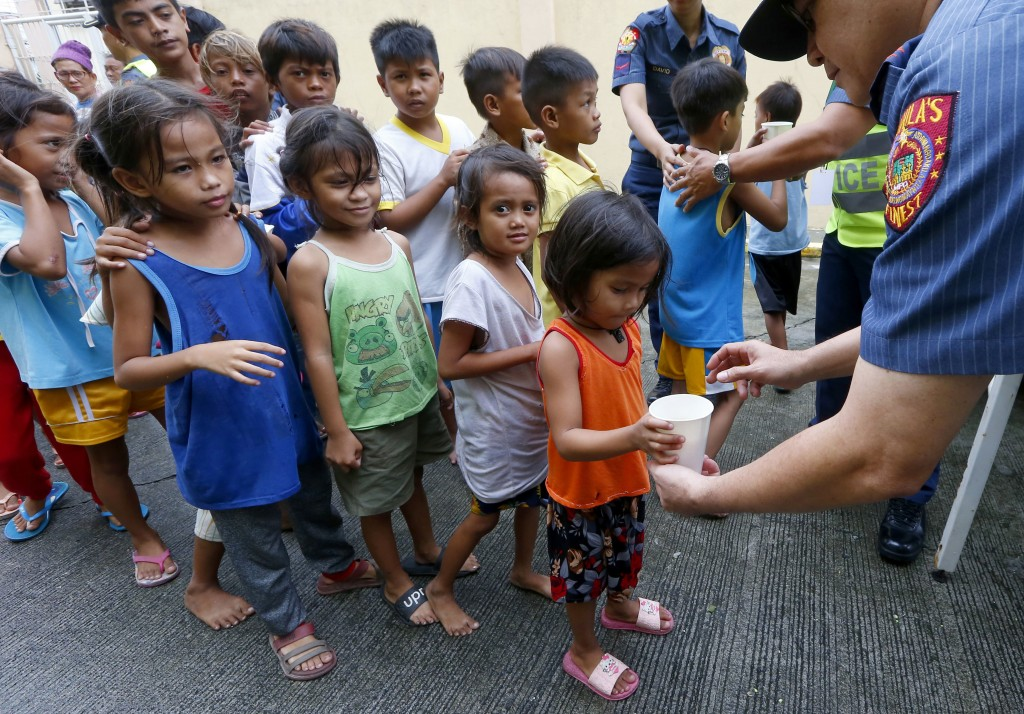 FILE - In this Saturday, Sept. 15, 2018, file photo, Manila police give out rice porridge to residents living along the coastal community of Baseco as