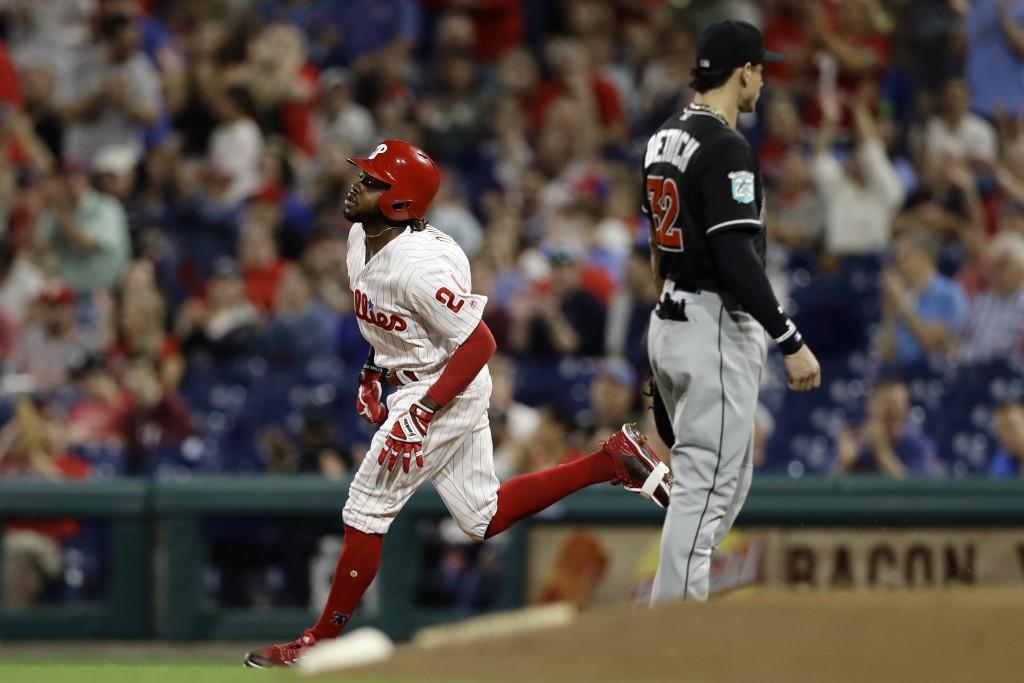 Philadelphia Phillies' Roman Quinn, left, rounds the bases past Miami Marlins first baseman Derek Dietrich, right, after hitting a home run off starti...