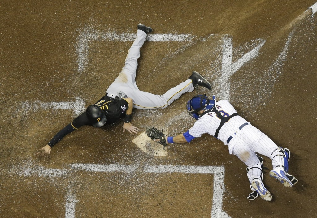 Pittsburgh Pirates' Jordan Luplow slides safely past Milwaukee Brewers catcher Manny Pina during the third inning of a baseball game Friday, Sept. 14,