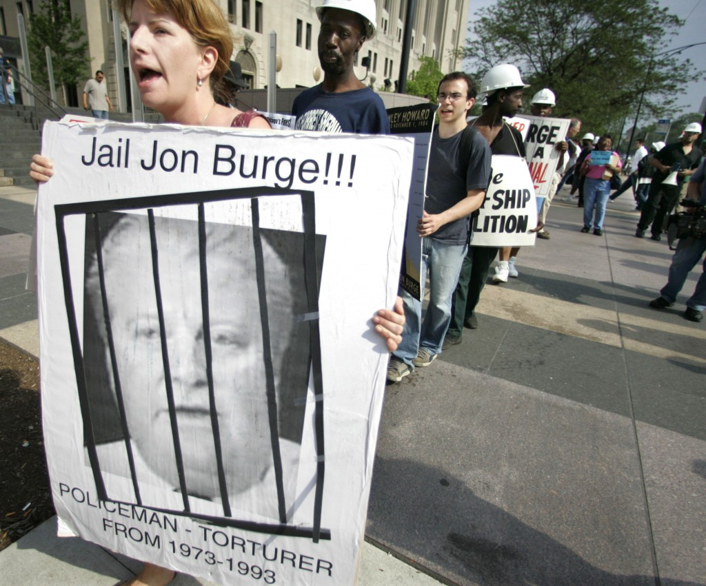 FILE - In this June, 16, 2006 file photo, Kristin Roberts, left, holds a sign of former Police Commander Jon Burge as she and others stage a protest o