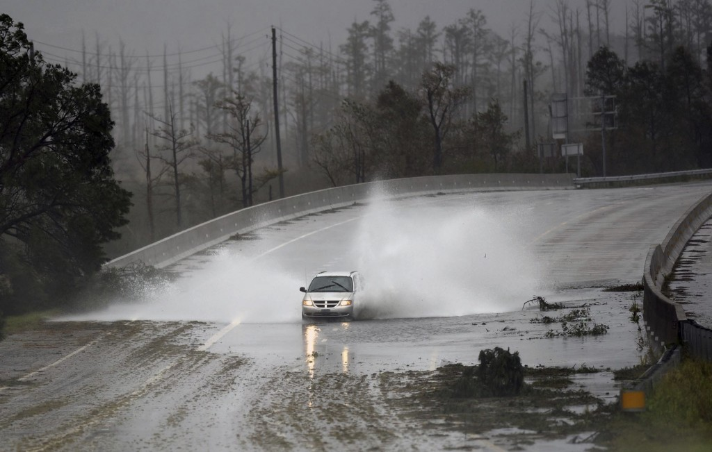 A car drives through water caused by the rain from Florence, now a tropical storm on U.S. 74/76 in Leland, N.C., Saturday, Sept.15, 2018. The rain fro
