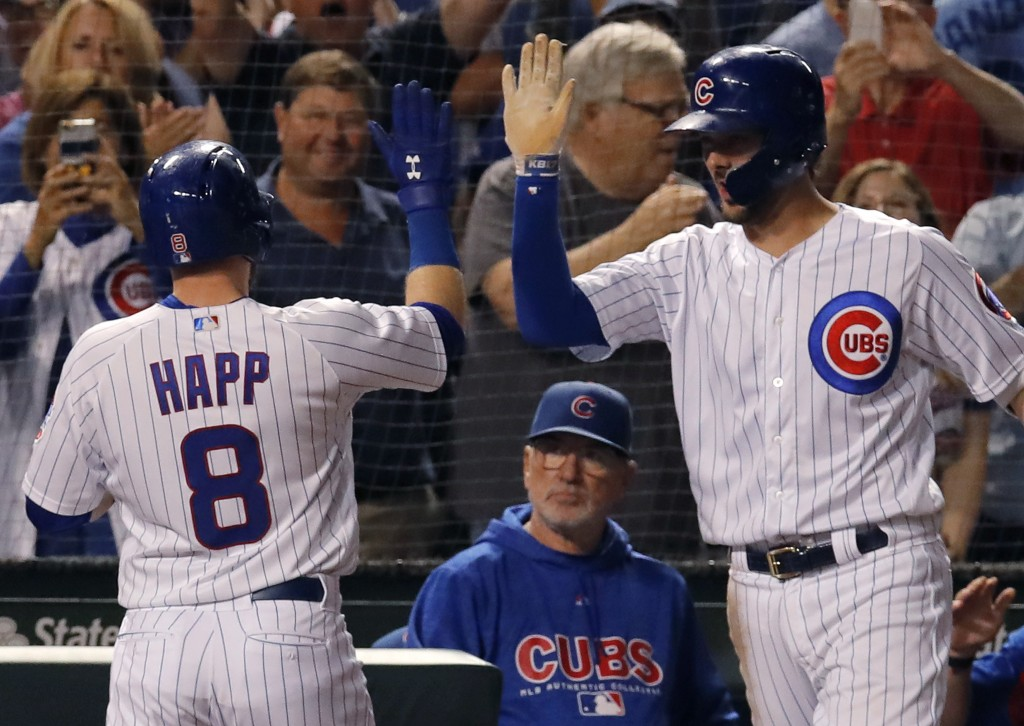 Chicago Cubs' Ian Happ, left, celebrates his three-run home run against the Cincinnati Reds with teammate Kris Bryant, right, as manager Joe Maddon lo